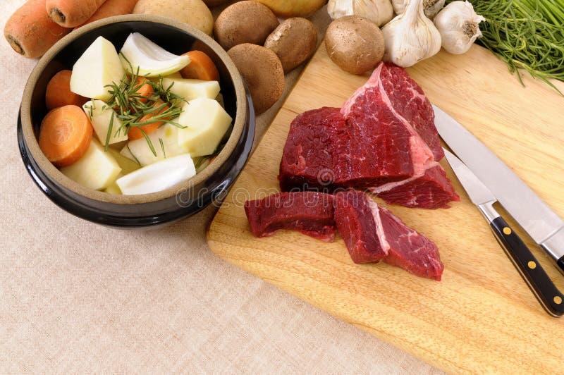 Zubereitung des Rindfleisches für Kasserolle oder des Eintopfgerichts mit Bestandteilen und Messer auf hölzernem hackendem Brett stockbild