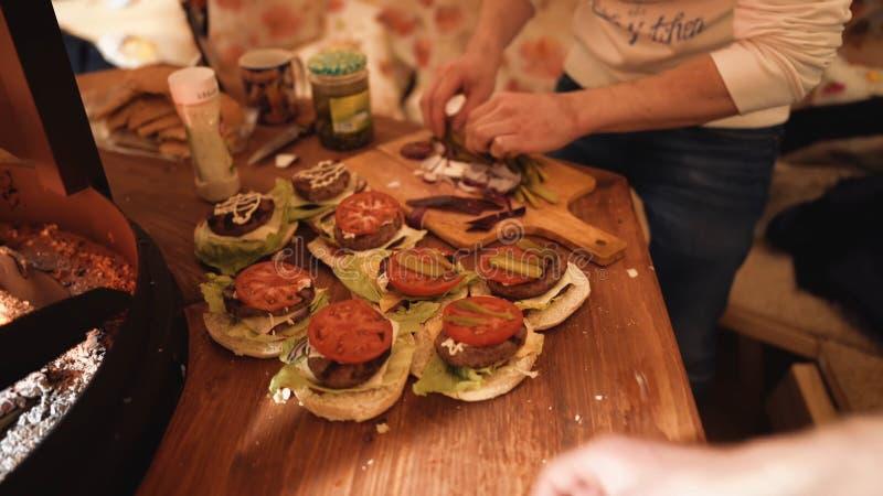 Zubereitung die Hamburger, Hamburger, Bestandteile für das Kochen von Burgern auf hölzernem hackendem Brett machend, Gemüse stockfotografie