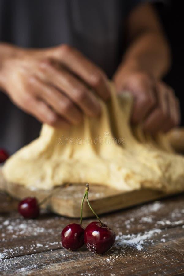 Zubereitung einer Koka de Cireres, ein Kirschflacher Kuchen stockfotos
