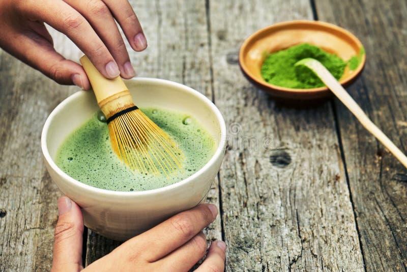 Zubereitung grünen matcha Tees unter Verwendung des traditionellen Bambusschneebesens auf Holztisch stockfotos