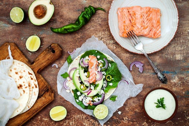 Zubereitung von gesunden Mittagessensnäcken Fischtacos mit gegrillten Lachsen, roter Zwiebel, frischen Salatblättern und Avocadok stockfotos