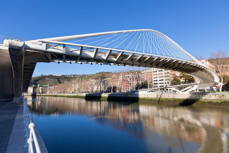 Zubizuri, the Campo Volantin Bridge, Bilbao, Spain. The Zubizuri, the Campo Volantin Footbridge in Bilbao, Spain, modern pedestrian tied arch crossing of the stock photography