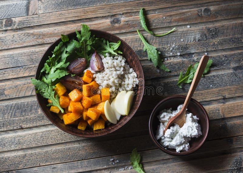 Zucca al forno, cipolle rosse e ciotola vegetariana dell'orzo sulla tavola di legno, vista superiore Alimento vegetariano fotografia stock