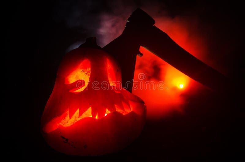 Zucca arancio spaventosa con gli occhi scolpiti e un sorriso con le candele brucianti e un'ascia su un fondo scuro con il cielo d immagine stock