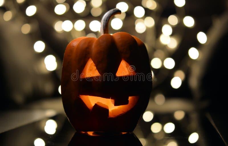 Zucca con gli occhi del taglio e bocca con una candela dentro su un fondo scuro - un simbolo di Halloween immagini stock