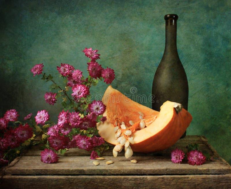 Zucca con i fiori di autunno immagine stock
