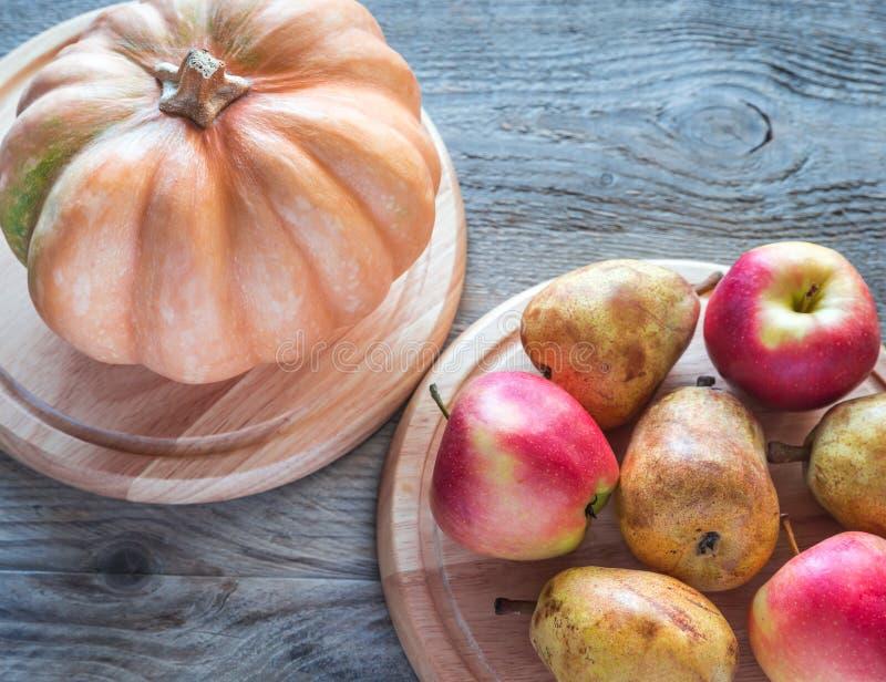 Zucca con le mele e le pere sui precedenti di legno fotografia stock