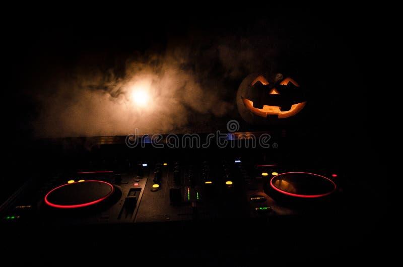 Zucca di Halloween su una tavola del DJ con le cuffie su fondo scuro con lo spazio della copia Decorazioni felici e musica di fes immagine stock