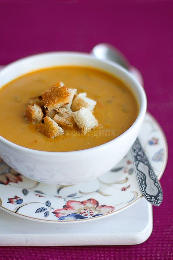 Zucca e minestra crema delle lenticchie con i crostini immagini stock