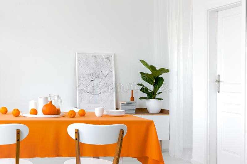 Zucca ed arance sulla tavola della sala da pranzo, mappa incorniciata accanto al mucchio dei libri sullo scaffale fotografia stock libera da diritti