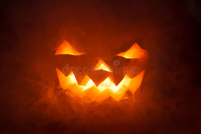 Zucca spaventosa di Halloween che guarda attraverso il fumo. fotografia stock