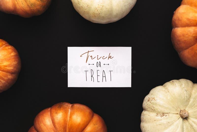 Zucche arancio e bianche con la carta di scherzetto o dolcetto royalty illustrazione gratis