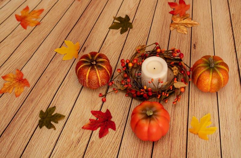 Zucche, foglie e candela della decorazione di caduta sul contesto della mussola fotografia stock libera da diritti