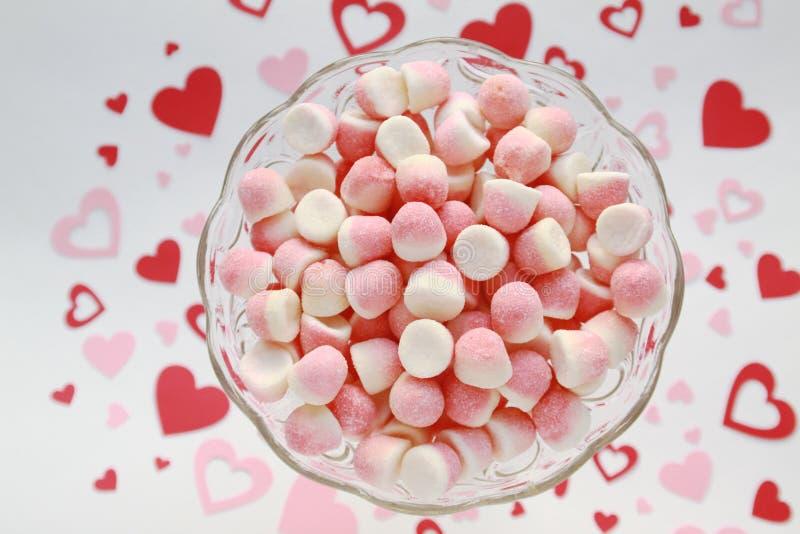 Zuccheri canditi in una ciotola di vetro su un fondo romantico immagini stock