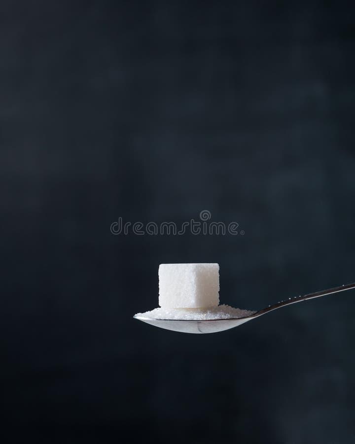 Zuccheri il cubo ed i cristalli in un cucchiaino d'argento sui precedenti scuri immagini stock