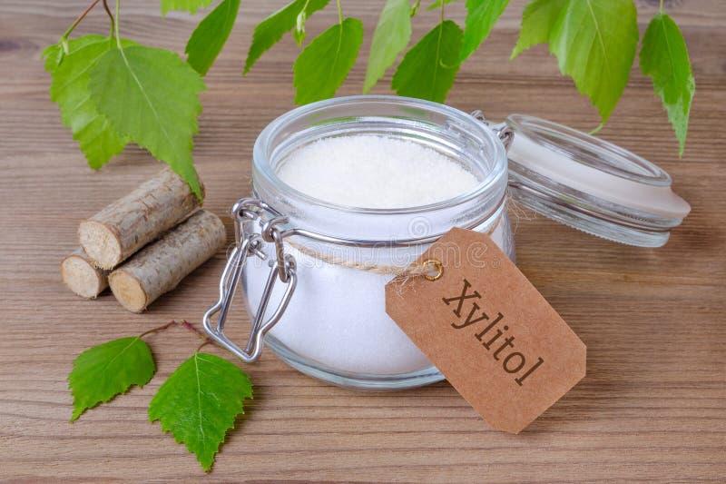 Zuccheri il xilitolo sostitutivo, un barattolo di vetro con lo zucchero della betulla, i liefs ed il legno immagini stock libere da diritti