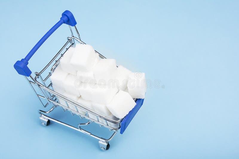 Zucchero bianco nel carrello su fondo blu Zucchero d'acquisto nel supermercato Copi lo spazio per testo fotografie stock