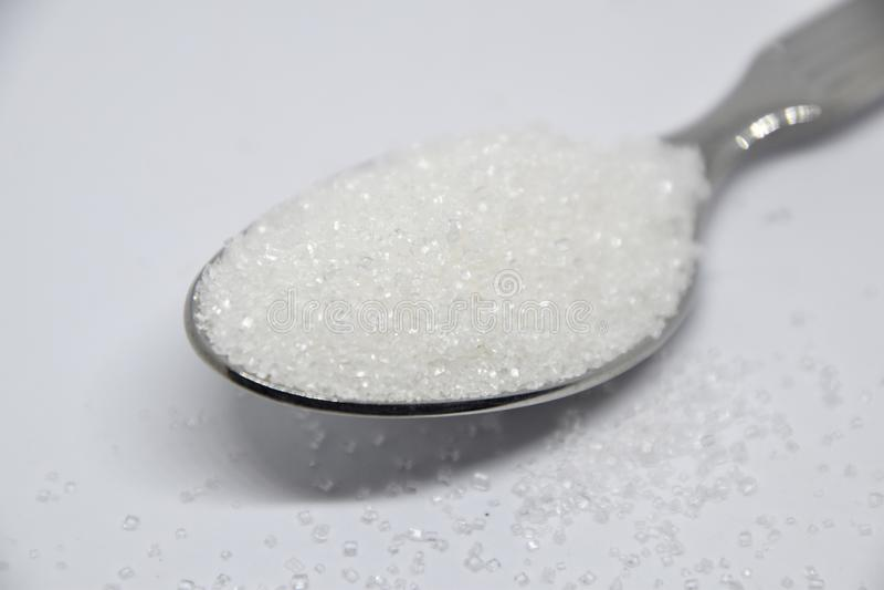 Zucchero bianco su un cucchiaino d'argento su fondo bianco immagini stock libere da diritti