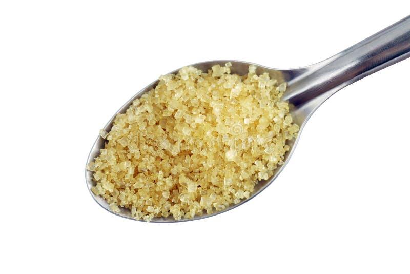 Zucchero in cucchiaio, zucchero da giallo dello zucchero granulato della canna da zucchero su un concetto inossidabile del cucchi fotografie stock