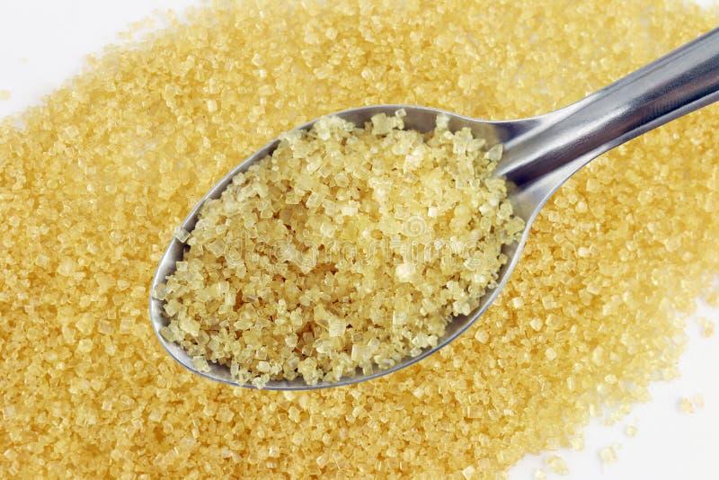 Zucchero in cucchiaio, zucchero da giallo dello zucchero granulato della canna da zucchero su un concetto inossidabile del cucchi fotografia stock libera da diritti