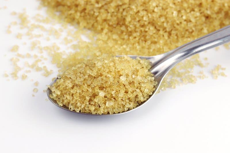 Zucchero, zucchero dalla canna da zucchero sul fondo di giallo del cucchiaio dell'acciaio inossidabile e dello zucchero granulato fotografie stock
