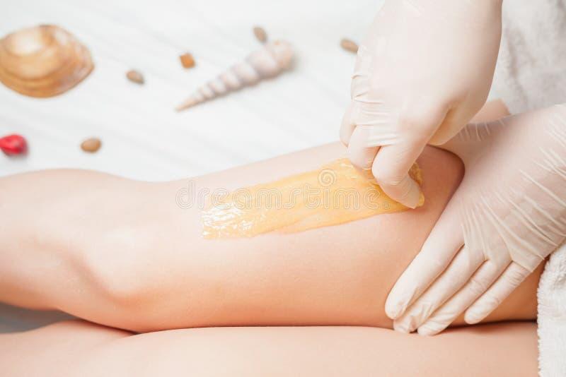 Zucchero della cura di pelle di epilation con zucchero liquido alle gambe immagini stock