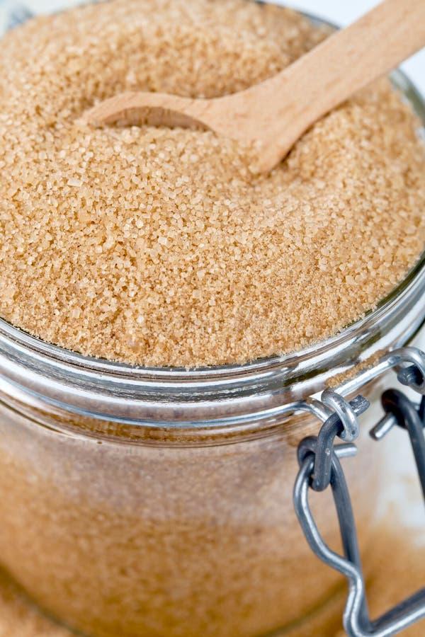 Zucchero di canna di Brown in barattolo di vetro e nell'immagine di legno del primo piano del cucchiaio fotografia stock