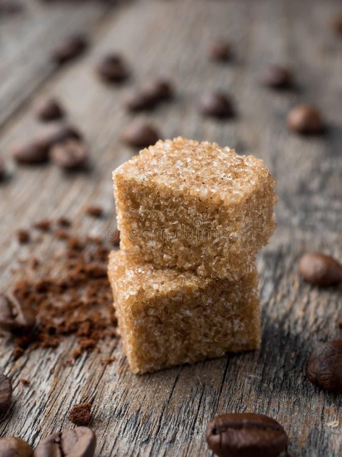 Zucchero di canna di Brown con i chicchi di caffè su fondo di legno rustico fotografie stock