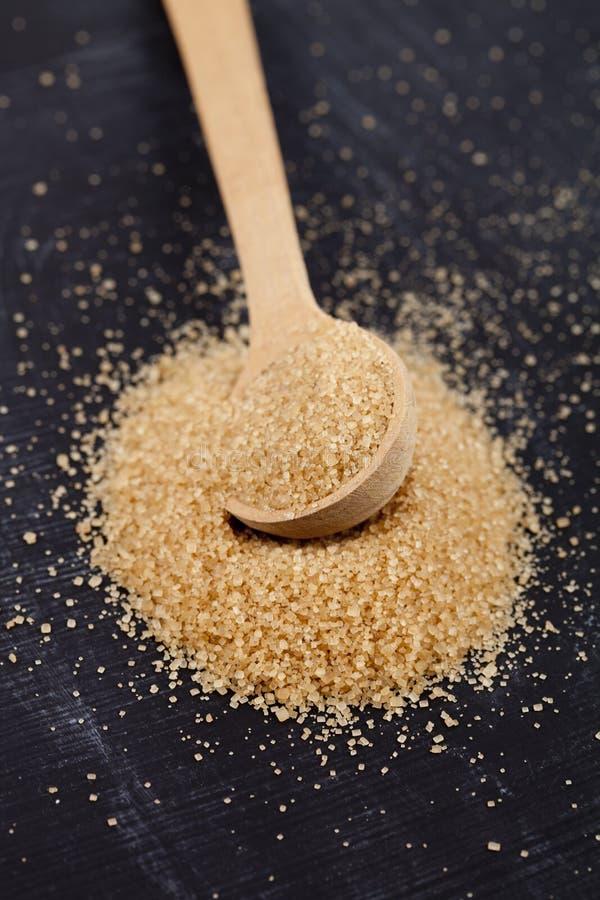 Zucchero di canna di Brown in cucchiaio di legno sul bordo nero fotografia stock libera da diritti