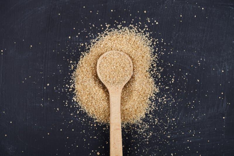Zucchero di canna di Brown in cucchiaio di legno sul fondo nero del bordo fotografia stock