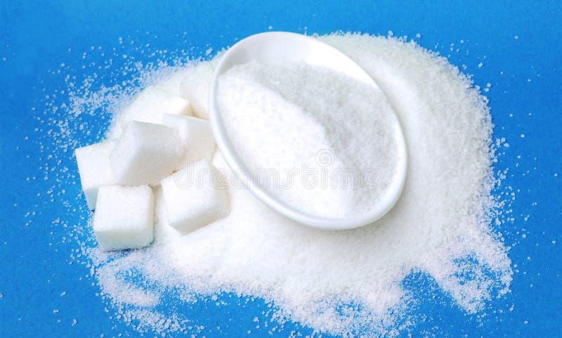 Zucchero di grumo e granulata su fondo blu immagini stock libere da diritti