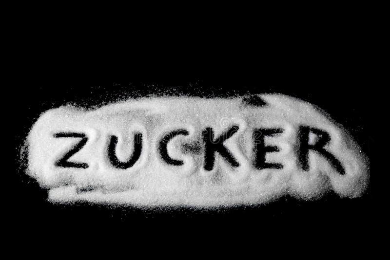 Zucchero di parola scritto in Deutsch di zucchero granulato bianco e di zucchero in polvere su fondo di pietra scuro, immagine stock