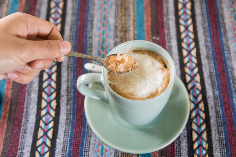 Zucchero di versamento sulla tazza di caffè fotografie stock libere da diritti
