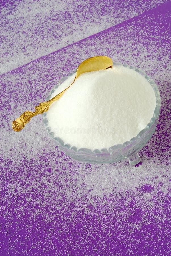 Zucchero granulato bianco puro su una priorità bassa rosso magenta fotografie stock libere da diritti