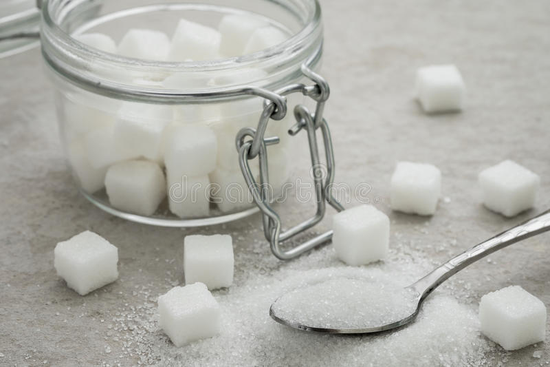 Zucchero sul barattolo di vetro e del cucchiaio immagine stock