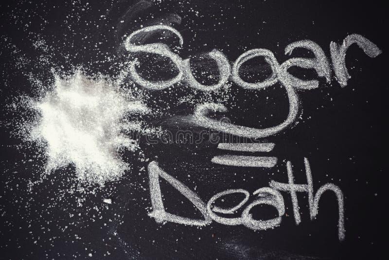 Zucchero sulla lavagna nera da sopra immagini stock