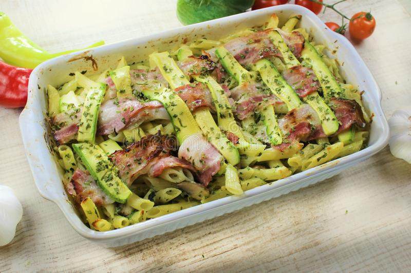 Zucchini and bacon baked pasta with cheese and Parmesan in the white pot on the white wooden table colorful vegetable. Baked in the oven stock images