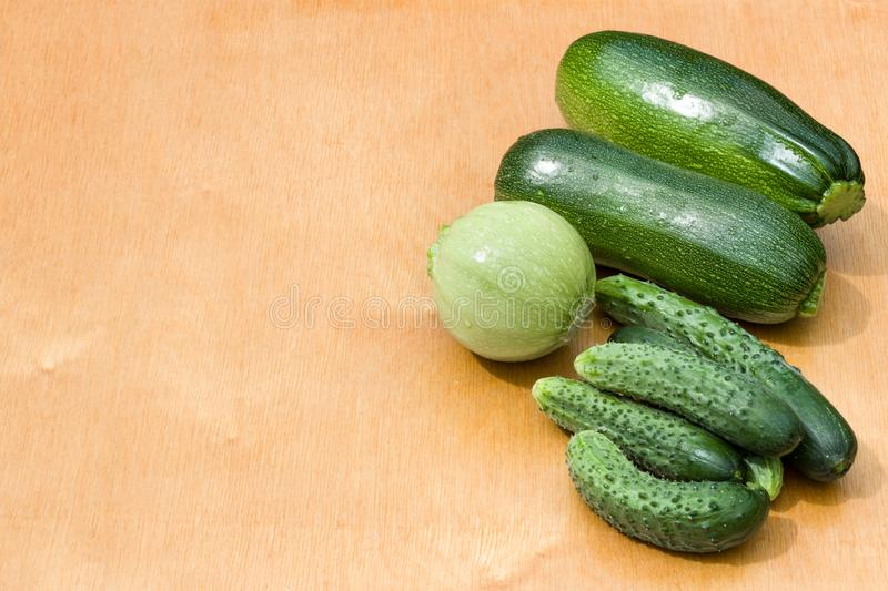 Courgettes, cucumbers from the garden beds on a wooden background. Country vegetables royalty free stock photography