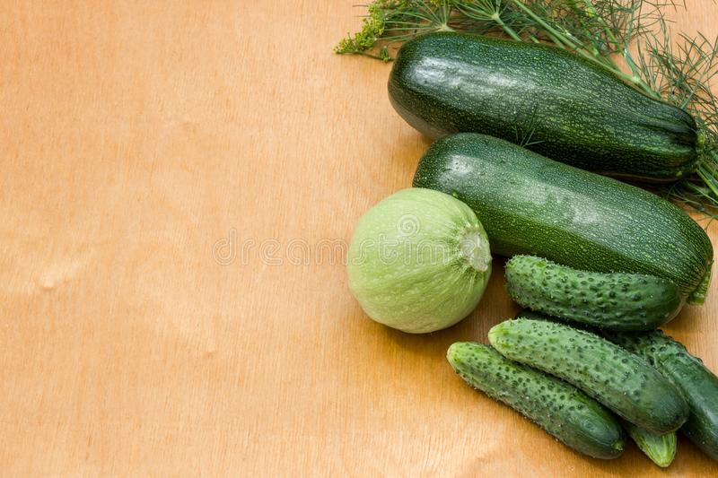 Courgettes, cucumbers from the garden beds on a wooden background. Country vegetables stock photos