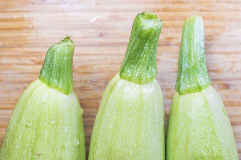 Zucchini drei auf einem hölzernen Küchenbrett stockbild
