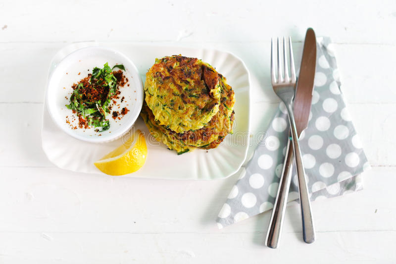 Zucchini fritters, vegetarian burger with coconut yogurt. Spices and lemon, dieting health meal stock photos