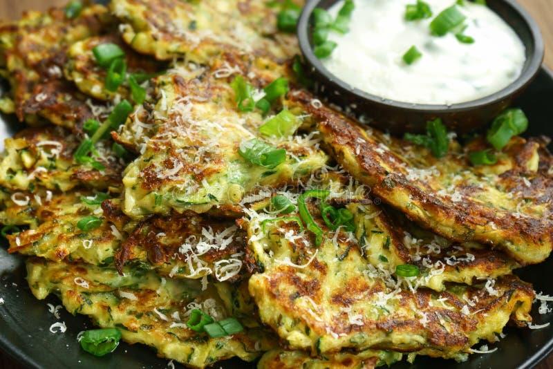 Zucchini fritters, vegetarian zucchini pancakes, served with fresh herbs and garlic yogurt sauce.  stock photo