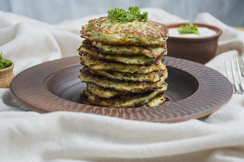Zucchini fritters, vegetarian zucchini pancakes, served with fresh herbs and sour cream, top view. Light background. Proper nutrition. Vegetarian cuisine stock photos