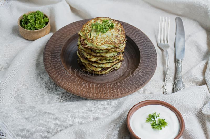 Zucchini fritters, vegetarian zucchini pancakes, served with fresh herbs and sour cream, top view. Light background. Proper nutrition. Vegetarian cuisine royalty free stock image