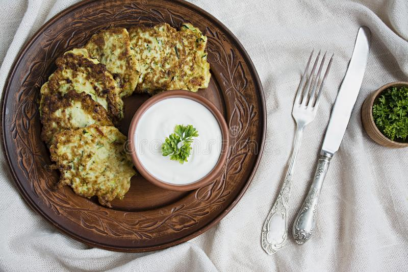 Zucchini fritters, vegetarian zucchini pancakes, served with fresh herbs and sour cream, top view. Light background. Proper nutrition. Vegetarian cuisine stock images