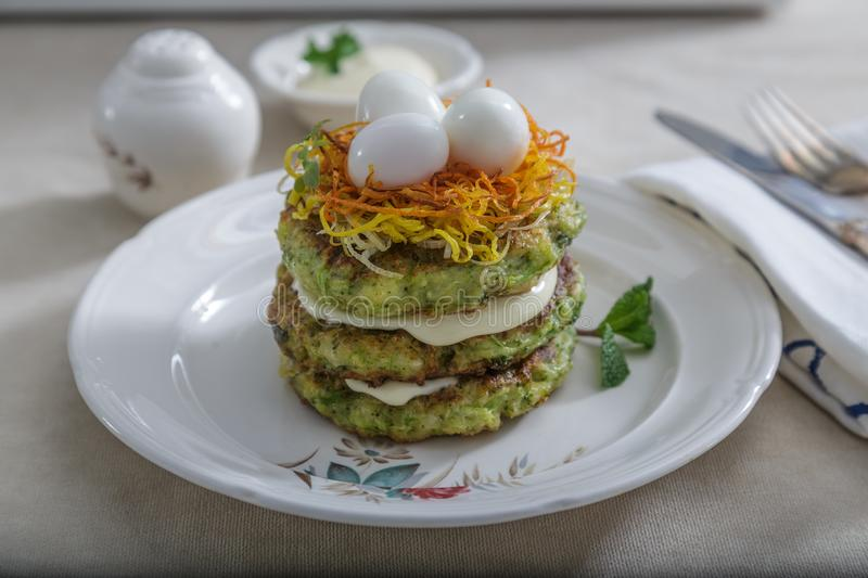 Zucchini fritters, vegetarian zucchini pancakes, served with quail eggs and carrots on top royalty free stock image