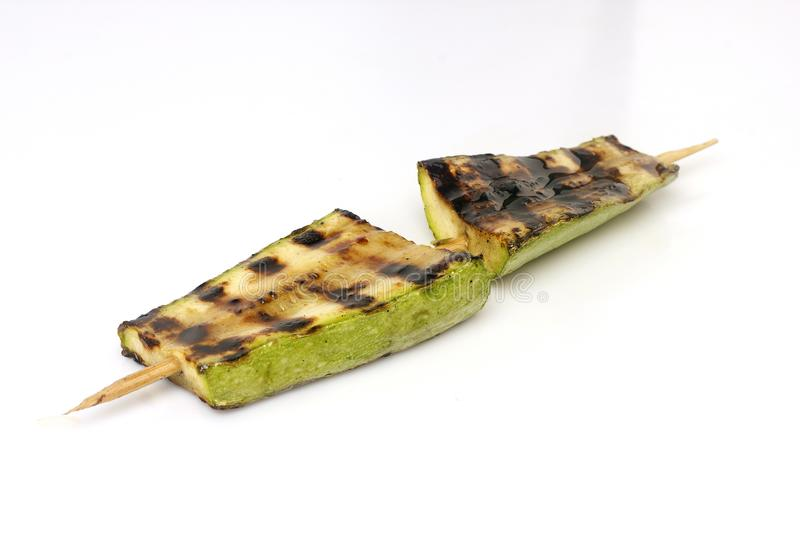 Zucchini grilled on a grill on a spit. On a white background royalty free stock image