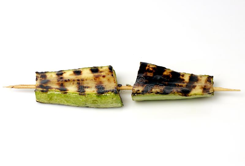 Zucchini grilled on a grill on a spit. On a white background stock photography