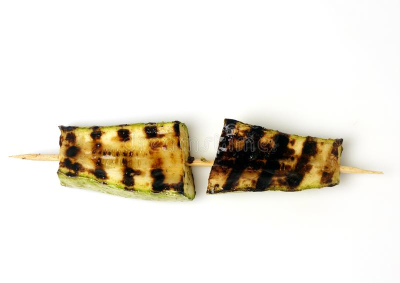 Zucchini grilled on a grill on a spit. On a white background stock photo