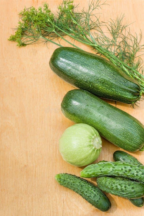 Zucchini, Gurken von den Gartenbetten auf einem hölzernen Hintergrund Landgemüse stockfotos